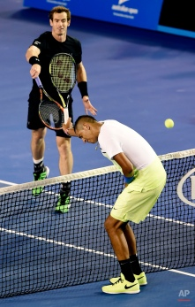 Andy Murray, left, of Britain hits the ball as Nick Kyrgios of Australia puts his racket up to protect himself during their quarterfinal match at the Australian Open tennis championship in Melbourne, Australia, Tuesday, Jan. 27, 2015. (AP Photo/Andy Brownbill)