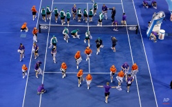 Ground staff dry the court surface of Rod Laver Arena in the rain delay during the women's singles final between Serena Williams of the U.S. and Maria Sharapova of Russia at the Australian Open tennis championship in Melbourne, Australia, Saturday, Jan. 31, 2015. (AP Photo/Lee Jin-man)