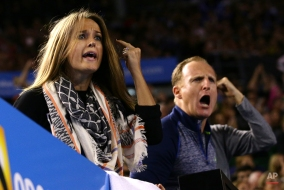 Kim Sears, fiancee of Andy Murray of Britain, left, and his fitness coach Matt Little, right, react as they watch his men's singles final against Novak Djokovic of Serbia at the Australian Open tennis championship in Melbourne, Australia, Sunday, Feb. 1, 2015.(AP Photo/Rob Griffith)