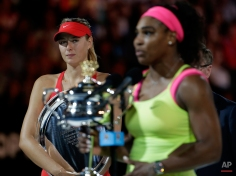 Maria Sharapova of Russia, left, looks at Serena Williams of the U.S. during the awarding ceremony after her women's singles final loss to Williams at the Australian Open tennis championship in Melbourne, Australia, Saturday, Jan. 31, 2015. (AP Photo/Vincent Thian)