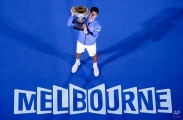 Novak Djokovic of Serbia poses with the trophy after defeating Andy Murray of Britain in the men's singles final at the Australian Open tennis championship in Melbourne, Australia, Sunday, Feb. 1, 2015. (AP Photo/Lee Jin-man)