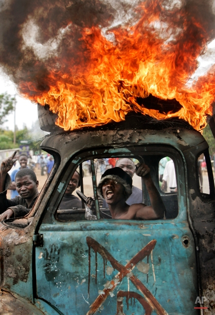 A Kenyan man sits in the cab of a destroyed truck used as a makeshift roadblock while a tyre burns on the roof, as he and others enforce the roadblock in Kisumu, Kenya, Tuesday, Jan. 29, 2008. (AP Photo/Ben Curtis)