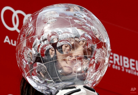 Anna Fenninger is seen through her alpine ski, women's World Cup overall trophy, at the World Cup finals in Meribel, France, Sunday, March 22, 2015. Fenninger successfully defended her overall World Cup and giant slalom titles after winning the season-ending GS race on Sunday. (AP Photo/Giovanni Auletta)