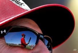 Cincinnati Reds' Brennan Boesch is reflected in manager Bryan Price's sunglasses as he warms up on deck during the second inning of a spring training baseball game against the Kansas City Royals, Saturday, March 7, 2015, in Surprise, Ariz. (AP Photo/Charlie Riedel)