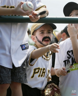 Roman Scolieri of Pittsburgh, wearing a fake mustache, for Pirates favorite Pedro Alvarez, yells into the dugout looking for autographs before a spring training exhibition baseball game against the Baltimore Orioles in Sarasota, Fla., Thursday, March 19, 2015. (AP Photo/Carlos Osorio)