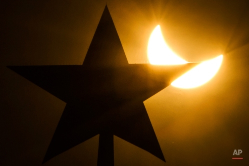 In this photo taken through a solar filter material, the moon blocks part of the sun during a solar eclipse as seen over Moscow Kremlin's Troitskaya (Trinity) tower, in Russia, on Friday, March 20, 2015. An eclipse is darkening parts of Europe on Friday in a rare solar event that won't be repeated for more than a decade.(AP Photo/Pavel Golovkin)