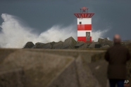 A man watches as the sea batters against a lighthouse during stormy weather at the entrance to the port of Scheveningen, near The Hague, Netherlands, Tuesday, March 31, 2015. A storm with wind speeds of up to 110 kilometers (68 miles) per hour passed over The Netherlands and Germany. (AP Photo/Peter Dejong)