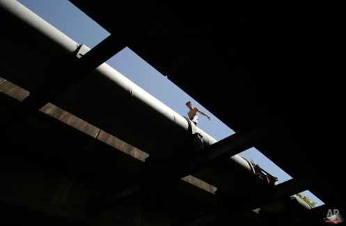 A Filipino man crosses a pipe in suburban Paranaque, south of Manila, Philippines on Tuesday, March 31, 2015. (AP Photo/Aaron Favila)