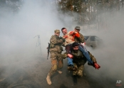 Instructors conduct first aid training during an exercise by tactical medicine for heads of Kiev districts and their deputies in Kiev, Ukraine, Tuesday, March. 31, 2015. (AP Photo/Sergei Chuzavkov)