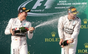 Mercedes driver Nico Rosberg, left, of Germany, sprays champagne on teammate Lewis Hamilton, of Britain, on the podium after the Australian Formula One Grand Prix at Albert Park in Melbourne, Australia, Sunday, March 15, 2015. Hamilton won the season-opening race ahead of Rosberg. (AP Photo/Rob Griffith)