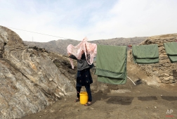 An Afghan girl hangs clothes to dry at her home on the outskirts of Kabul, Afghanistan, Tuesday, March 10, 2015. The war-torn country faces the challenges of poverty, unemployment, and a lack of infrastructure. (AP Photo/Rahmat Gul)
