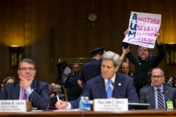 A CodePink demonstrator is escorted out by a member of the Capitol Police on Capitol Hill in Washington, Wednesday, March 11, 2015, after attempting to interrupt the testimony by Secretary of State John Kerry, center, and Defense Secretary Ash Carter, left, before the Senate Foreign Relation Committee. America's top national security officials faced questions on Capitol Hill about new war powers being drafted to fight Islamic State militants, Iran's sphere of influence and hotspots across the Mideast. (AP Photo/Pablo Martinez Monsivais)