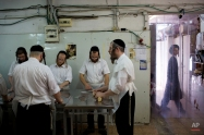Ultra-Orthodox Jews prepare special matzoh, a traditional handmade Passover unleavened bread, at a bakery in Bnei Brak near Tel Aviv, Israel, Tuesday, March 31, 2015. Jews are forbidden to eat leavened foodstuffs during the Passover holiday, which celebrates the biblical story of the Israelites' escape from slavery and exodus from Egypt. (AP Photo/Oded Balilty)