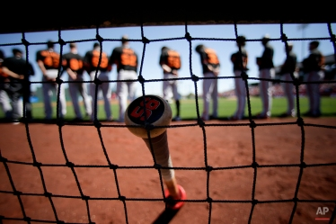 San Francisco Giants center fielder Gary Brown's bat rests near the dugout during the national anthem before a spring training baseball exhibition game against the Los Angeles Angels in Tempe, Ariz., on Saturday, March 21, 2015. (AP Photo/Chris Carlson)