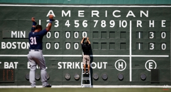 Boston Red Sox intern Tim Batesole changes the manual scoreboard during the sixth inning of an exhibition spring training baseball game against the Minnesota Twins, Wednesday, March 18, 2015, in Fort Myers, Fla. (AP Photo/Brynn Anderson)