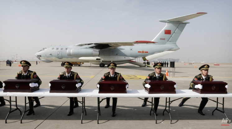 Chinese honor guards place caskets containing the remains of Chinese soldiers during the handing over ceremony at the Incheon International Airport in Incheon, South Korea, Friday, March 20, 2015. (AP Photo/Ahn Young-joon)