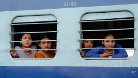 Passengers of a moving train react as they move past the site of a train accident near Bachhrawan village, in the northern Indian state of Uttar Pradesh, Friday, March 20, 2015. Police and rescue workers used gas cutters to rip apart the wreckage to find people who were feared to be trapped after three coaches of a passenger train derailed in northern India. (AP Photo/Rajesh Kumar Singh)