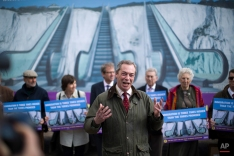Nigel Farage the leader of the UK Independence Party (UKIP) speaks to the media backdropped by a poster unveiled for his party's immigration campaign launch for the British general election, in St Margaret's Bay, near Dover, on the south east coast of England, Tuesday, March 31, 2015. Britain goes to the polls for a general election on May 7, 2015. (AP Photo/Matt Dunham)