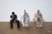 """A gallery worker installs sculptures by the late Israeli artist Ofra Zimbalista on the Art Market gallery rooftop for a show titled """"Purifcation,"""" in Tel Aviv, Israel, Tuesday, March 10, 2015. (AP Photo/Oded Balilty)"""