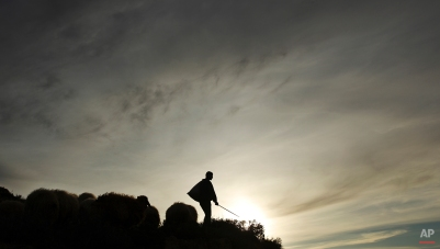 A Palestinian shepherd and his livestock are seen on a mountain on the outskirts of the West Bank city of Ramallah, Feb. 4, 2009. (AP Photo/Muhammed Muheisen)