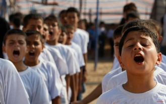 Palestinian boys stand lined up and chant as they exercise on the beach, during a Hamas summer camp in Gaza City, June 15, 2009. (AP Photo/Hatem Moussa)