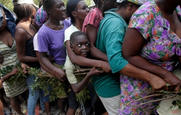 Sonsonne Semtembre, 9, center, hangs on to a tree branch as he tries to stay in line with others to receive disaster relief at the US 82nd Airborne Division's forward operating base in Port-au-Prince, Jan. 20, 2010. (AP Photo/Jae C. Hong)