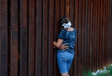 A woman, who declined to give her name, is hugged by her husband as they chat between the border fence separating Nogales, Ariz., and Nogales, Sonora, Mexico, on July 28, 2010. (AP Photo/Jae C. Hong)