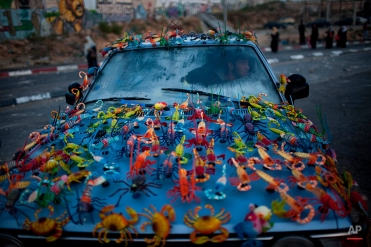 Magnets for sale are displayed on the car of a Palestinian man at the Kalandia checkpoint, between Jerusalem and the West Bank city of Ramallah, on Aug. 13, 2010. (AP Photo/Bernat Armangue)