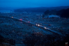 Japanese vehicles pass through the ruins of the leveled city of Minamisanriku, Japan. Last year's devastating earthquake and tsunami destroyed more than half the buildings in this once-scenic, blue-collar fishing town, knocked out power and water, and left residents wondering if their community could ever rebuild on March 15, 2011. The disaster left around 19,000 people dead. (AP Photo/David Guttenfelder