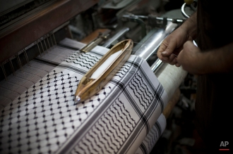 A Palestinian worker in a family owned workshop that makes checkered head scarves, or keffiyehs, works a loom, in the West Bank city of Hebron, July 13, 2011. (AP Photo/Bernat Armangue)