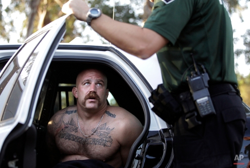 Andrew Lozano, a member of the Vagos motorcycle gang, talks to a Fontana police officer after he was arrested in an early morning raid in Fontana, Calif., on Oct. 6, 2011. Hundreds of law enforcement officers have fanned out across Southern California and arrested at least 12 members and leaders of the Vagos motorcycle club, seizing weapons and drugs. (AP Photo/Jae C. Hong)