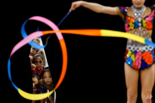 Members of the junior national team watch Jazzy Kerber, foreground, compete during the rhythmic all-around finals at the USA Gymnastics Championships in San Jose, Calif., June 27, 2012. (AP Photo/Jae C. Hong)
