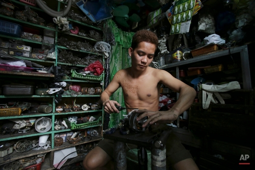 A Filipino technician works on an electric fan at a repair shop in Manila, Philippines on Wednesday, March 11, 2015. The shop charges P300 (about US$7) for minor repairs. (AP Photo/Aaron Favila)