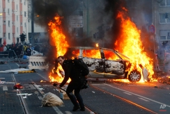 A police car burns after clashes between demonstrators and police Wednesday, March 18, 2015 in Frankfurt, Germany. The Blockupy alliance said activists plan to try to blockade the new headquarters of the ECB to protest against government austerity and capitalism. (AP Photo/Michael Probst)