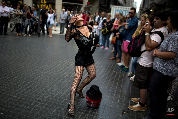 A street artist dances tango in Buenos Aires, Argentina, Tuesday, Jan. 20, 2015. Tango is a partner dance that originated in the 1890's along the Rio de la Plata, the border between Uruguay and Argentina. UNESCO approved in 2009, a joint proposal by the two nations to include the dance in its Intangible Cultural Heritage List. (AP Photo/Rodrigo Abd)