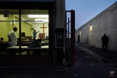Pastor Emmanuel Okoli, standing next to a cross, gives a sermon to homeless people at Outreach Mission Center as a man, right, urinates in an alley in the Skid Row area of Los Angeles, March 21, 2013. (AP Photo/Jae C. Hong)