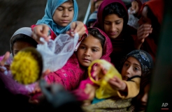 Pakistani children jostle to receive free food distributed at the shrine of Sufi saint Barri Imam in the suburbs of Islamabad, Pakistan, Monday, March 2, 2015. Hundreds of poor and homeless people receive food from different shrines in Pakistan. (AP Photo/B.K. Bangash)