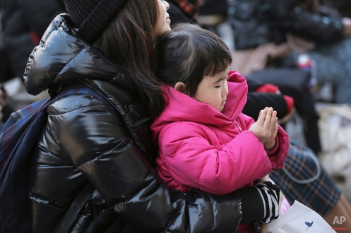 A girl joins her hands in prayer with her mother to mourn for victims of the March 11, 2011 earthquake and tsunami during a special memorial event in Tokyo, Wednesday, March 11, 2015. Still struggling to recover, the tsunami-hit region of northeastern Japan marked the fourth anniversary of the disaster Wednesday with simultaneous moments of silence along the coast. (AP Photo/Eugene Hoshiko)