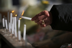 A woman lights a candle in prayer to mourn for victims of the March 11, 2011, earthquake and tsunami during a special memorial event in Tokyo, Wednesday, March 11, 2015. (AP Photo/Eugene Hoshiko)