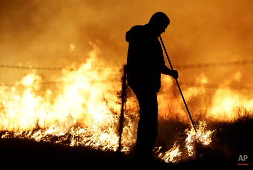 Micah Garber lights a controlled fire in a pasture near Lawrence, Kan., Monday, March 23, 2015. Fires are commonly set in the spring to remove old growth and improve pasture quality. (AP Photo/Orlin Wagner)