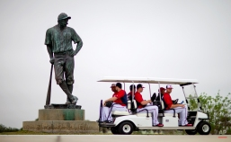 Washington Nationals players ride a golf cart past a Casey at the Bat statue outside Space Coast Stadium on their way to the practice fields for a spring training baseball workout, Wednesday, Feb. 25, 2015, in Viera, Fla. (AP Photo/David Goldman)
