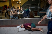 A man takes a nap as a group of women gather inside a fast food restaurant in downtown Buenos Aires, Argentina, Friday, Feb. 20, 2015. (AP Photo/Rodrigo Abd)