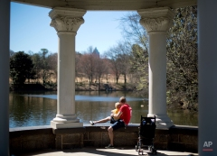 Keith Johnson, right, sits with his son Tommy, 2, both of Lilburn, Ga., while watching ducks swim by in Piedmont Park, Monday, March 16, 2015, in Atlanta. (AP Photo/David Goldman)