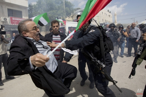 Palestinians protester is pushed by Israeli border policemen during a protest marking the Land Day in the West Bank village of Hawara near Nablus, Monday, March 30, 2015. Land Day commemorates riots on March 30, 1976, when six people were killed during a protest by Israeli Arabs whose property was annexed in northern Israel to expand Jewish communities. (AP Photo/Majdi Mohammed)