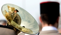 The reflection of a French soldier and the Neuve Chapelle Indian Monument is reflected in the bell of a musical instrument during a WWI commemoration ceremony at the Neuve Chapelle Indian Memorial in Neuve Chapelle, France on Friday, March 13, 2015. The Memorial commemorates over 4,700 Indian soldiers and workers who lost their lives on the Western Front during WWI and have no known grave. (AP Photo/Virginia Mayo)