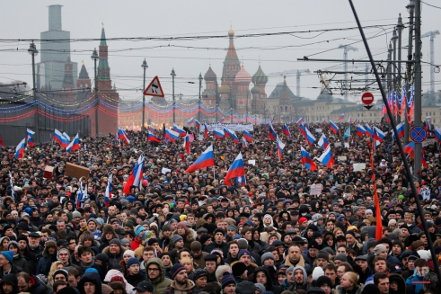 People carry Russian national flags during a march in memory of opposition leader Boris Nemtsov who was gunned down on Friday, Feb. 27, 2015 near the Kremlin. (AP Photo/Dmitry Lovetsky)