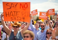 """Protestors hold up signs during a rally against a contentious """"religious freedom"""" bill, Tuesday, March 17, 2015, in Atlanta. The Georgia Senate gave decisive approval to the bill, one of a wave of measures surfacing in at least a dozen states that critics say could provide legal cover for discrimination against gays and transgender people. (AP Photo/David Goldman)"""