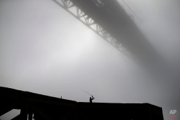 A fisherman throws his line under the April 25th bridge by the Tagus riverbank during a foggy morning, in Lisbon, Tuesday, March 10, 2015. The name of the bridge was given after the Carnations revolution that restored the democracy in Portugal in April 1974. (AP Photo/Francisco Seco)