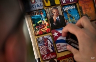 """A person looks at magnets for sale inside a souvenir shop, one showing an image of U.S. President Barack Obama smelling a cigar, at a market in Havana, Cuba, Monday, March 16, 2015. U.S. and Cuban officials are meeting Monday in last-minute closed door negotiations in Havana, in hopes of restoring full diplomatic relations before the Summit of the Americas in April. The magnet the person is touching reads in Spanish: """"Here, nobody gives up,"""" a popular quote attributed to Cuba's late revolutionary hero Camilo Cienfuegos. (AP Photo/Ramon Espinosa)"""