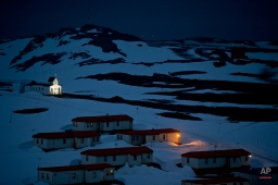 In this Jan. 20, 2015 photo, a church is lit in the town of Villa Las Estrellas on King George Island, Antarctica. Geologists are entranced by Antarctica's secrets. Clues to answering humanity's most basic questions are locked in this continental freezer the size of the United States and half of Canada: Where did we come from? Are we alone in the universe? What's the fate of our warming planet? (AP Photo/Natacha Pisarenko)